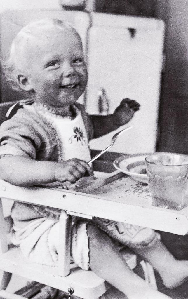 Schwarz-weiß Foto eines Kleidkindes auf einem Hochstuhl beim Essen