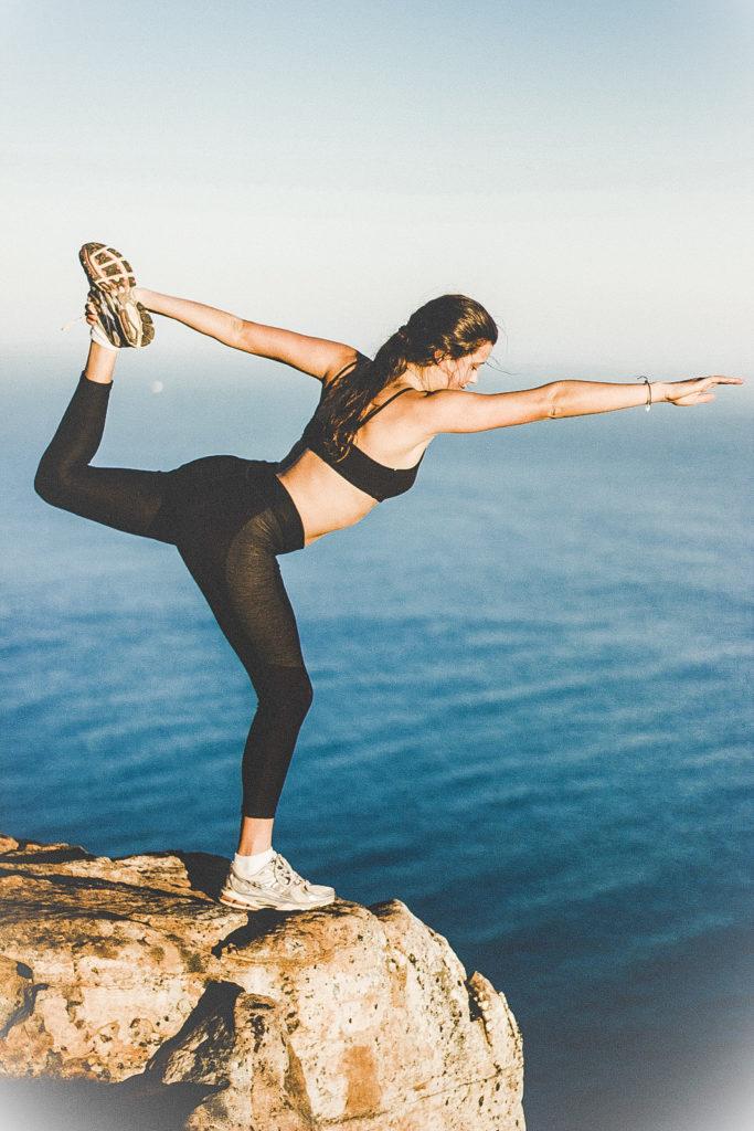 Frau in schwarzer Sportkleidung macht eine Dehnübung mit dem Bein auf einer Klippe am Meer