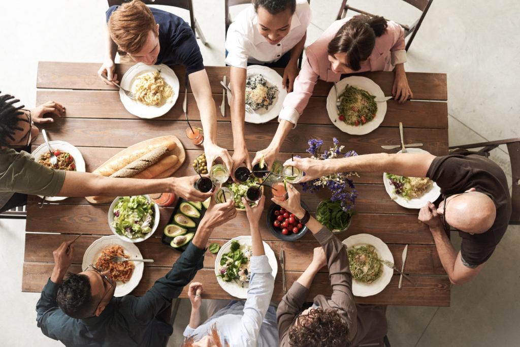 Acht Menschen sitzen am einem gut gedeckten Tisch und stoßen an