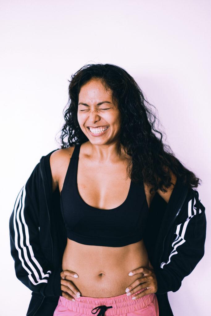 Lachende Frau mit geschlossenen Augen in Sport-BH und Hose