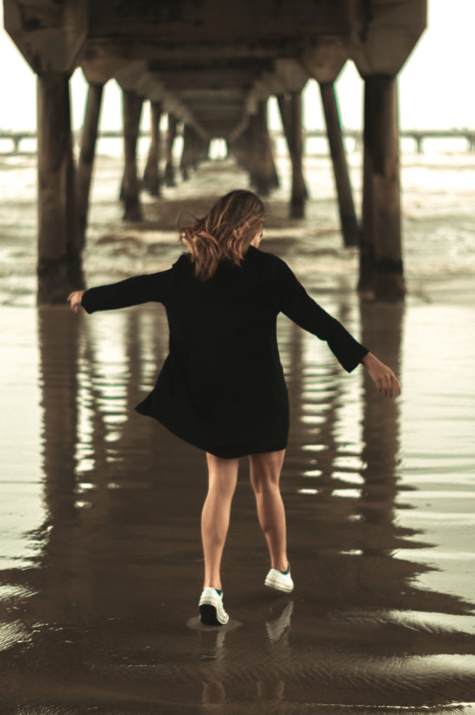 Mädchen im schwarzen Hemd läuft unter einer Holzbrücke