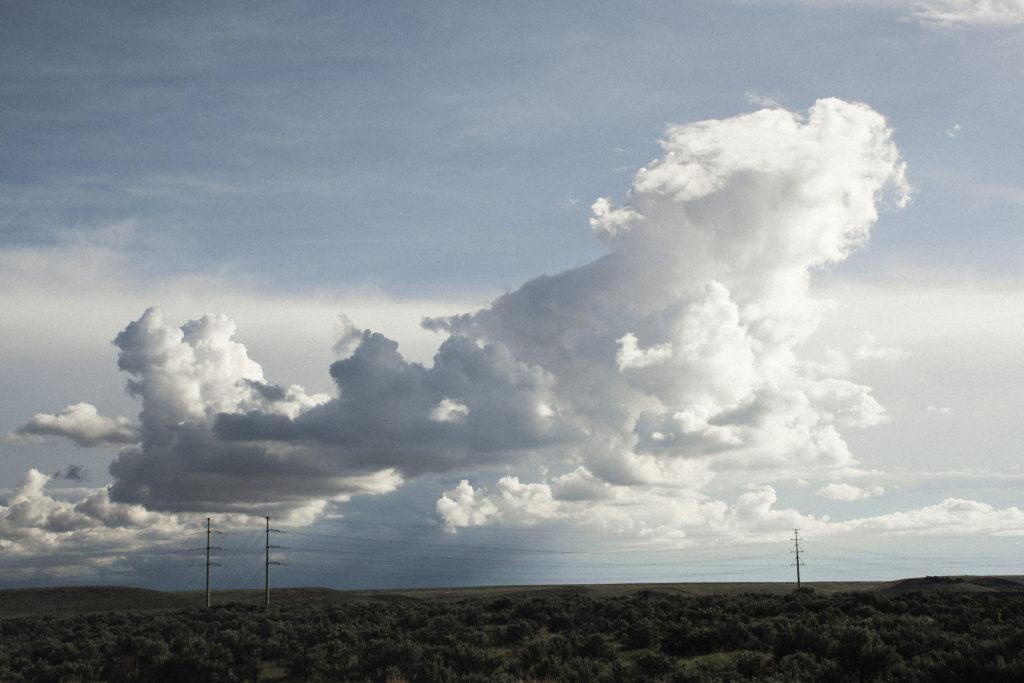 Große Wolken über einer grünen kargen Landschaft.